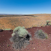 Red rock lines a large volcanic crater, one of many in an area known as Diamond Craters in southeastern Oregon. The area contains dozens of basaltic lava flows, cinder cones, and maars ranging in age from 6,000 to 60,000 years old.