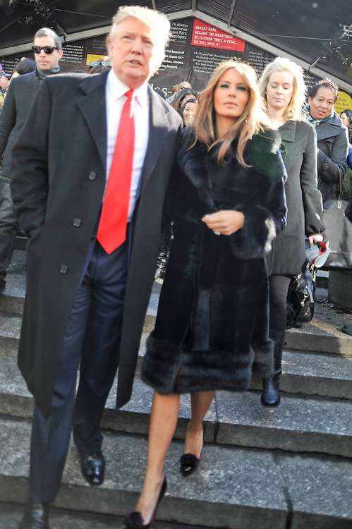 Donald Trump in a red tie and Melania Trump in a black fur belted coat ...