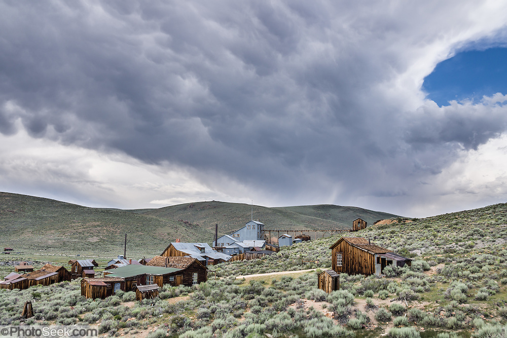 "Afternoon thunderstorm clouds loom over historic Bodie and its Standard Stamp Mill. Bodie is California's official state gold rush ghost town. Bodie State Historic Park lies in the Bodie Hills east of the Sierra Nevada mountain range in Mono County, near Bridgeport, California, USA. After W. S. Bodey's original gold discovery in 1859, profitable gold ore discoveries in 1876 and 1878 transformed ""Bodie"" from an isolated mining camp to a Wild West boomtown. By 1879, Bodie had a population of 5000-7000 people with 2000 buildings. At its peak, 65 saloons lined Main Street, which was a mile long. Bodie declined rapidly 1912-1917 and the last mine closed in 1942. Bodie became a National Historic Landmark in 1961 and Bodie State Historic Park in 1962."