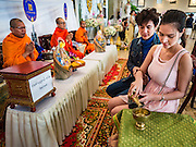 "14 FEBRUARY 2017 - BANGKOK, THAILAND:  Buddhist monks blesses a couple's marriage during a mass wedding in the Bang Rak district in Bangkok. Bang Rak is a popular neighborhood for weddings in Bangkok because it translates as ""Village of Love."" (Bang translates as village, Rak translates as love.) Hundreds of couples get married in the district on Valentine's Day, which, despite its Catholic origins, is widely celebrated in Thailand.     PHOTO BY JACK KURTZ"