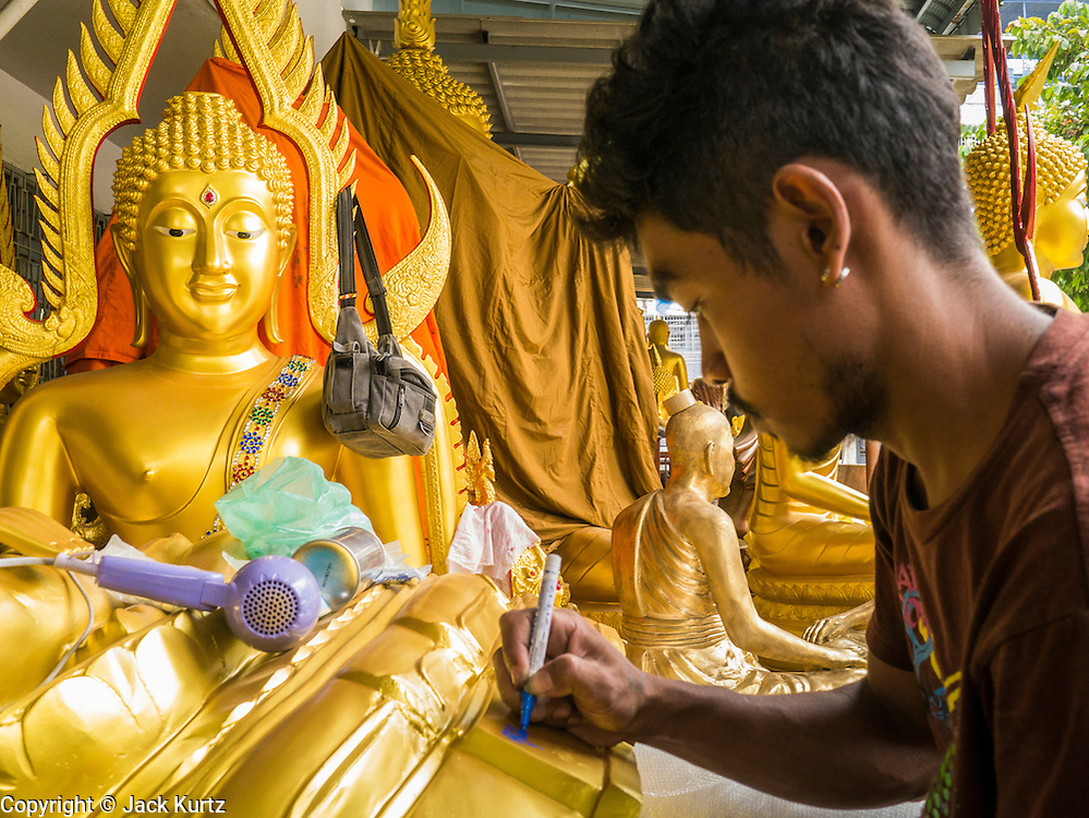 """12 NOVEMBER 2012 - BANGKOK, THAILAND:   A worker details a statue of the Buddha at a workshop Bamrung Muang Street in Bangkok. Thanon Bamrung Muang (Thanon is Thai for Road or Street) is Bangkok's """"Street of Many Buddhas."""" Like many ancient cities, Bangkok was once a city of artisan's neighborhoods and Bamrung Muang Road, near Bangkok's present day city hall, was once the street where all the country's Buddha statues were made. Now they made in factories on the edge of Bangkok, but Bamrung Muang Road is still where the statues are sold. Once an elephant trail, it was one of the first streets paved in Bangkok. It is the largest center of Buddhist supplies in Thailand. Not just statues but also monk's robes, candles, alms bowls, and pre-configured alms baskets are for sale along both sides of the street.    PHOTO BY JACK KURTZ"""
