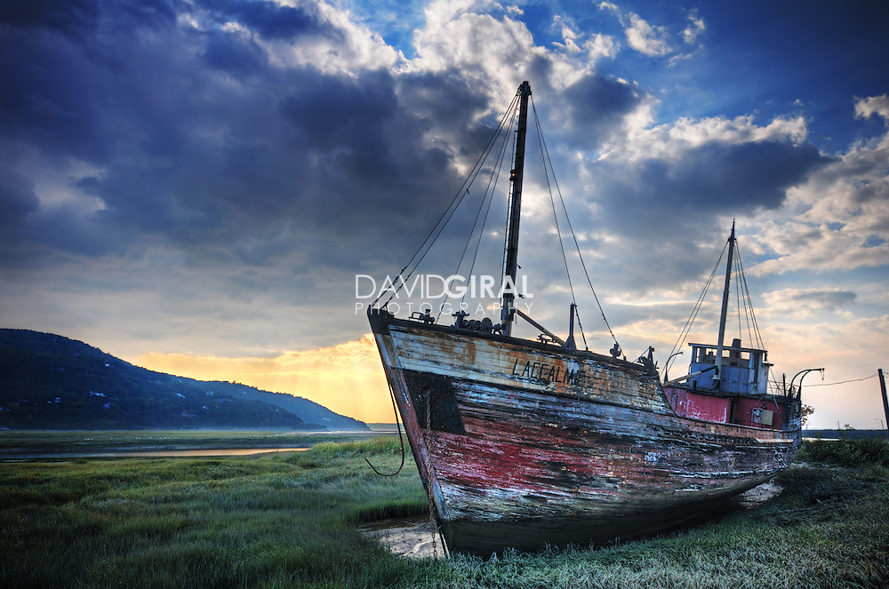Shipwreck on the shoreline by a beautiful morning, near Baie St-Paul, in Charlevoix region of Quebec