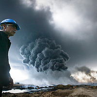 A South Oil Company employee looks on as smoke rises following a pipeline explosion south of Basra in al Faw, Iraq. According to people at the scene, the blast may have been caused by insurgents who have repeatedly attacked Iraq's oil infrastructure in the past. March 2004.