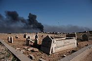 Iraq, Mosul: Smoke rises from a bombed area behind a cemetery in western Mosul. Alessio Romenzi