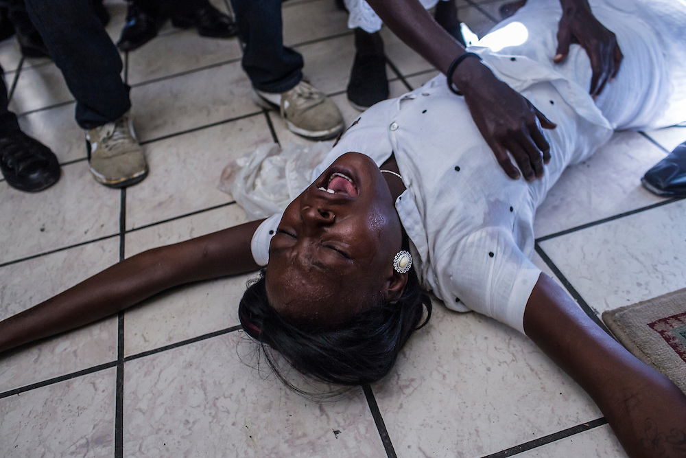 Bertha Nicolas, 20, collapses in grief at the funeral of her brother Jolin Nicolas, 19, on Monday, December 22, 2014 in Port-au-Prince, Haiti. Jolin Nicolas was killed by police while participating in anti-government protests on December 13.