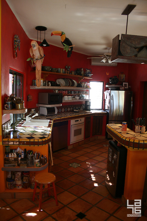 Red kitchen is part of a home, decorated by feng shui rules. The home is a beach front home in Los Barriles, Baja California Sur. <br />