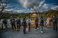 East Asian tourists, here mostly from China and Thailand, finish up selfies in front of Kinkaku-Ji Golden Pavillion in the designated photo spot before returning to the circuit that leads, one-way only, through the garden and eventually to the parking lot where the souvenir shop and tourist buses wait. Kyoto, Japan.