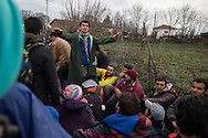Moin, Macedonia - 14.03.2016      <br /> <br /> A refugees ask the others to sit down and keep kalm. Many refugees left the camp in Idomeni on the Greek- Macedonian border where they are partially stranded for weeks . With a March of Hope and they went to the point at which ended the Macedonian border fence and crossed the border there. Their path led through rough terrain, including crossing a cold river. In the Macedonian village Moin heavily armed police and military forces stopped the refugees. Present journalists were immediately taken into custody while the refugees were driven away in military transport.<br /> <br /> Ein Fluechtling bittet die anderen sich zu setzen und ruhig zu bleiben. Zahlreiche Fluechtlinge verlie&szlig;en das Camp in Idomeni an der griechisch-mazedonischen Grenze wo sie teilweise seit Wochen gestrandet sind. Mit einem March of Hope zogen sie zu dem Punkt an dem der mazedonische Grenzzaun endete und &uuml;berquerten dort die Grenze. Ihr Weg fuehrte durch unwegsames Gelaende inklusive eines kalten Flusses. In dem mazedonischen Dorf Moin stoppten schwer bewaffnete Polizisten und Militaers den Fliehenden. Anwesende Journalisten wurde umgehend in Gewahrsam genommen waehrend die Fluechtlinge wurde in Militaertransportern weggefahren. <br /> <br /> Foto: Bjoern Kietzmann