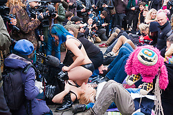 London, December 12th 2014. Porn and sex workers gather outside the Houses of Parliament for a mass sex simulation and face-sitting event in rotest against newly outlawed sex acts in the making of pornography in the UK. Under new Audiovisual Media Services Regulations 2014 rules, such acts as facesitting, spanking and female ejaculation are, among others, now banned from being shown  porn watched online. PICTURED: A woman sits on the face of another as the press scrum zooms in.