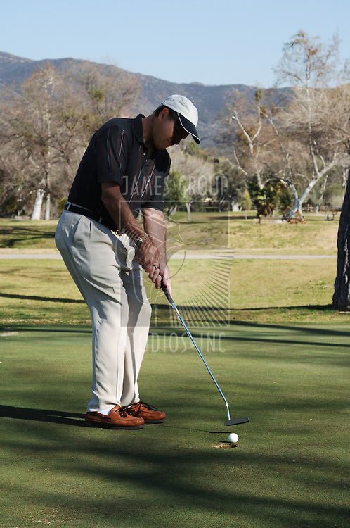 Golfer putting a golfball into the hole on a golf course putting green