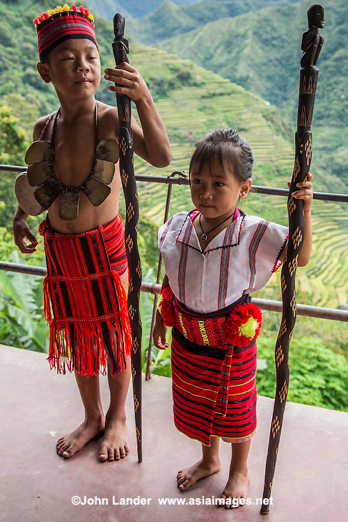 """Ifugao Tribe Indigenous Children posing in native costume in front of Batad Rice Terraces - a UNESCO world heritage site. Ifugao means """"earth people"""" or """"from the hills"""" who inhabit the mountains of the Philippines Cordilleras. Igorot is the collective name of these indigenous tribes who inhabit these regions"""