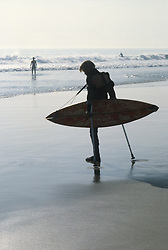 Surfer with one leg entering the ocean