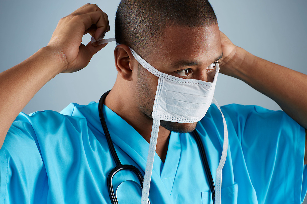 A portrait series representing the intense emotions that Doctors face.  An African American male Doctor wearing a white surgical mask, stethoscope, and blue medical scrub suit shown.