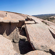 """Atop Enchanted Rock, looking towards Little Rock. Explore a large pink granite dome at Enchanted Rock State Natural Area, between Fredericksburg and Llano, Texas, USA. Enchanted Rock is a fascinating exfoliation dome (with layers like an onion), rising 425 feet (130 m) above its surroundings to elevation of 1825 feet (556 m) above sea level, in the Llano Uplift. Geologically, the exposed rock (monadnock or inselberg, """"island mountain"""") is part of a pluton (bubble of rock slowly crystallized from magma) within the billion-year-old igneous batholith, Town Mountain Granite (covering 62 square miles mostly underground), which intruded from a deep pool of hot magma 7 miles upwards into the older metamorphic Packsaddle Schist. The overlying sedimentary rock (Cretaceous Edwards limestone) eroded away to expose the prominent domes seen today: Enchanted Rock, Little Rock, Turkey Peak, Freshman Mountain, and Buzzard's Roost. This panorama was stitched from 3 overlapping photos."""