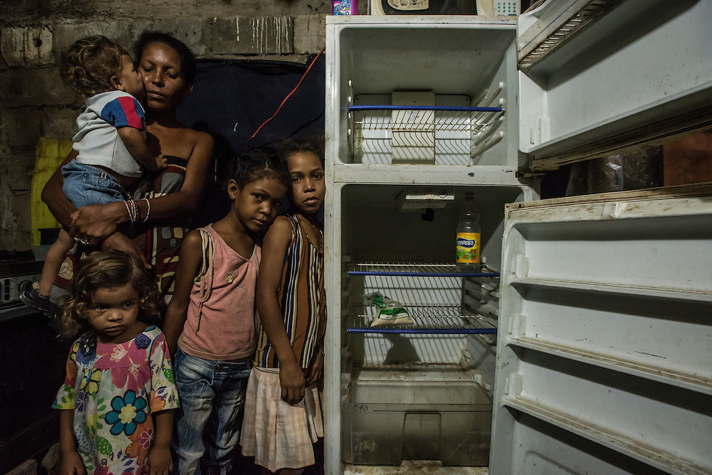 """CUMANÁ, VENEZUELA - JUNE 16, 2016: Leidy Cordova, a 37-year-old mother, poses for a portrait with four of her five children: Abran, 1, Deliannys, 3, Eliannys, 6, and Milianny, 8-years old. The entire family went the entire day without eating.  They hadn't eaten since lunchtime the day before...a soup made by boiling chicken skin and fat,  that is sold for a much cheaper price than  chicken at the butcher.  Inside their home, a cinderblock structure on the edge of the highway, a broken refrigerator was empty except for half a bag of corn flour and a bottle of vinegar. That was the only food they had in their entire house, and Ms. Cordova was worried about if she would be able to find a way to feed her children tomorrow.  """"My kids tell me they're hungry,"""" said Ms. Cordova as her family looked on. """"And I all can say to them is to grin and bear it."""" PHOTO: Meridith Kohut"""