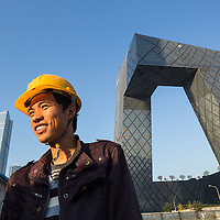 China, Beijing, Portrait of construction worker standing beneath steel and glass exterior of CCTV Building