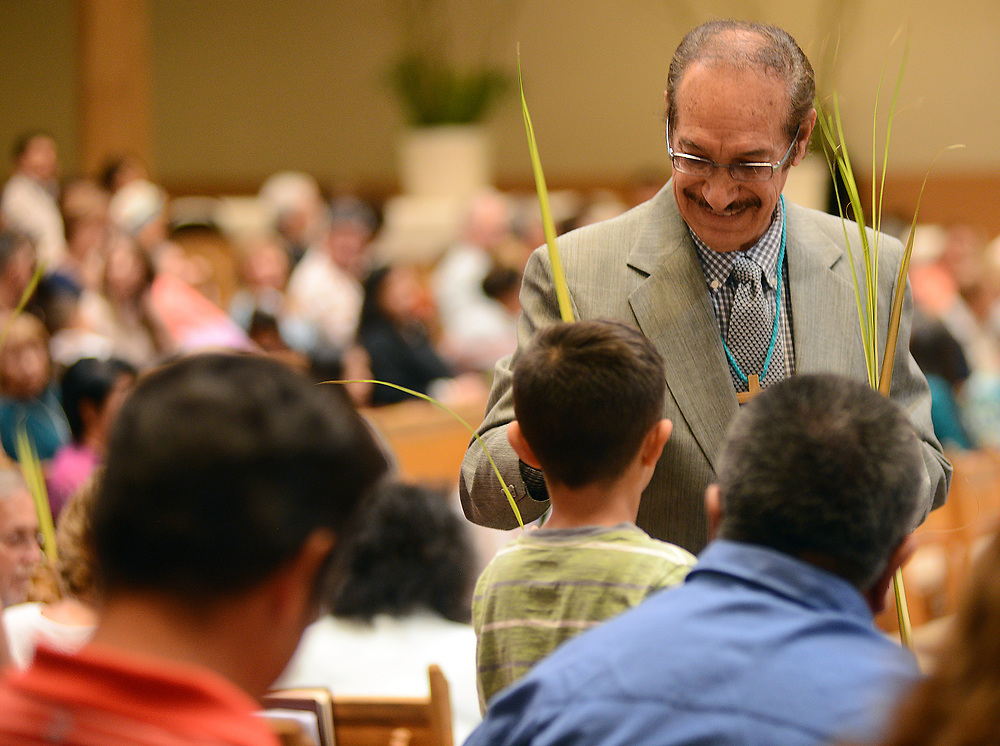 apl040917c/ASECTION/pierre-louis/JOURNAL 040917<br /> Usher Gilbert Benavidez,, hands  palms to parishioners before the 12:15 pm Mass at Our Lady of the Most Holy Rosary Catholic Church on Albuquerque West Mesa. Palm Sunday marks the beginning of Holy Week for Christians. Photographed on Sunday April 9, 2017. .Adolphe Pierre-Louis/JOURNAL