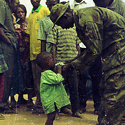A soldier helps a displaced child with water to drink