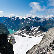 Jostedalsbreen National Park, Norway, protects the largest ice cap in continental Europe. Glaciers feed the turquoise lake Lovatnet at center left. Above the village of Loen on Innvikfjorden arm of Nordfjord (seen on right), ascend Skåla, the highest tidewater mountain in Norway. Between Tjugen camping and Loenvatnet, park at the pay lot and ascend to Skålatårnet (Skåla Tower, a DNT lodge) steeply on a well marked trail. Stepping stones greatly improve footing on the upper portion protected within Jostedalsbreen National Park (nasjonalpark). Hike 5 hours up and 3 hours down on a strenuous ascent of over 1800 meters (6000 feet). Loen is in Stryn municipality, Sogn og Fjordane county, Norway. Panorama stitched from 8 overlapping photos.