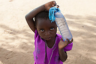 Maria (6) from Mishoni Village, Nsanje District, Malawi, carries a bottle of water during the drought of 2016.