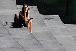London, July 18th 2016. A woman basks in the sun near City Hall as temperatures soar past 29ºC in London.