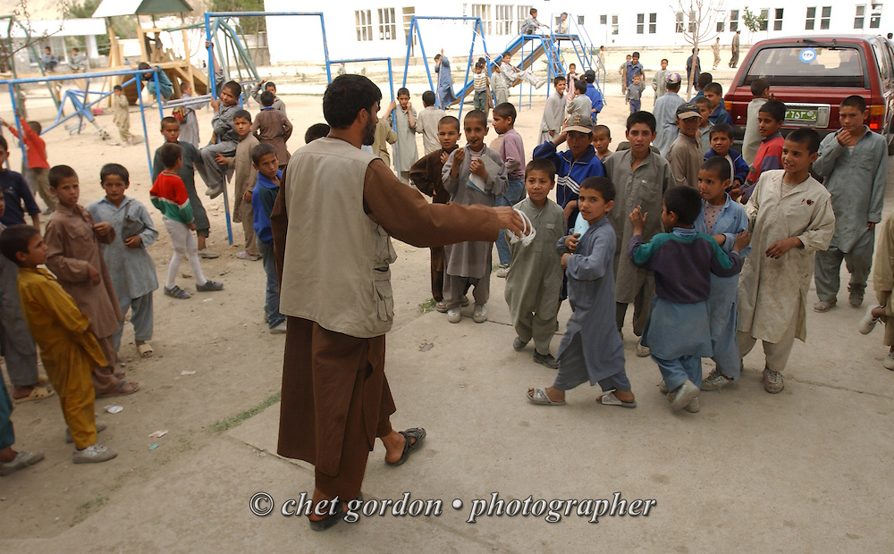 """A counselor scatters Afghan orphan boys outside the Alowdin Orphanage for boys and girls on Saturday, May 25, 2002. A humanitarian mission organized by The Geshundheit Instititute, founded by Dr. Hunter """"Patch"""" Adams, Lufthansa Cargo, and DHL Worldwide Express collaborated to ship medicines, food and orthopedic supplies to the Indira Ghandi Children's Hospital, clinics and orphanages in Kabul. The German NGO (Non Governmental Organization) Hammer Forum supervised the distribution of the donated supplies from various non-profit organizations in the U.S. and The Netherlands."""