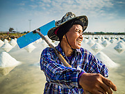 22 FEBRUARY 2017 - BAN LAEM, PETCHABURI, THAILAND: A salt field worker with her rake during the salt harvest in Petchaburi province of Thailand, about two hours south of Bangkok on the Gulf of Siam. Salt is collected in coastal flats that are flooded with sea water. The water evaporates and leaves the salt in large pans. Coastal provinces south of Bangkok used to be dotted with salt farms, but industrial development has pushed the salt farms down to remote parts of Petchaburi province. The harvest normally starts in early February and lasts until early May, but this year's harvest was delayed by a couple of weeks because of unseasonable rain in January that flooded many of the salt collection ponds.    PHOTO BY JACK KURTZ