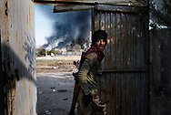 Iraq, Mosul: In Dawwasah neighbourhood an Iraqi soldier look back at his comrades as smoke rises from houses burned by ISIS fighters as they retreat. Alessio Romenzi
