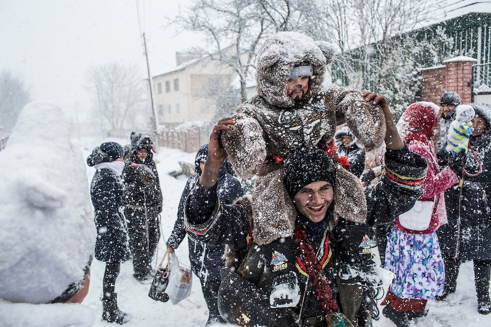 Revelers in costume celebrate the Malanka Festival as a heavy snow falls on Thursday, January 14, 2016 in Krasnoilsk, Ukraine. The annual celebrations, which consist of costumed villagers going in a group from house to house singing, playing music, and performing skits, began the previous sundown, went all night, and will last until evening.
