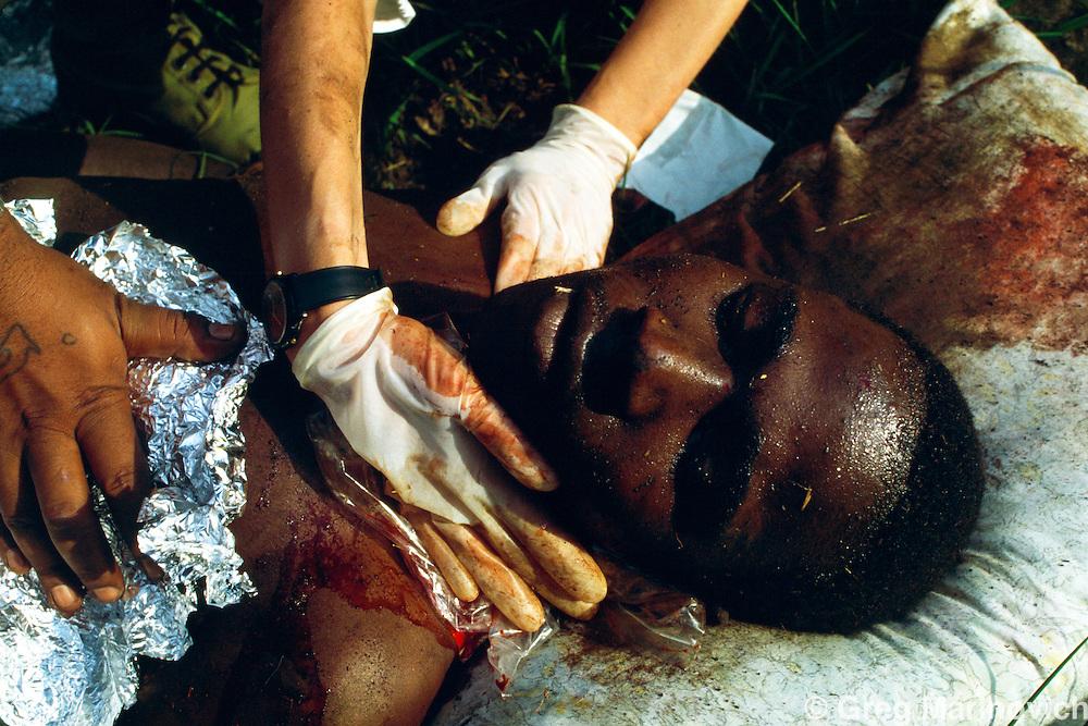 KwaMashu township, KwaZulu Natal, South Africa 1994. Medics try to save a man shot from a car in KwaMashu township.