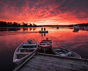 Two lobstermen head to their boat on a zodiac under a stunning sunrise in Round Pond, Maine.