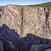 Painted Wall View, Black Canyon of the Gunnison National Park, near Montrose, Colorado, USA. Pressurized molten rock was forced into 1.7-billion-year-old metamorphic rock, forming pink pegmatite stripes on Colorado's highest cliffs. With two million years to work, the Gunnison River and weathering have sculpted a vertical wilderness of rock, water, and sky. This panorama was stitched from 11 overlapping photos.