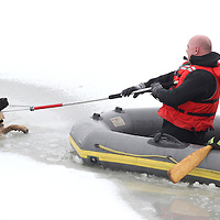 1221 Muncie, Ind. firefighters work on rescuing a German Shepherd after it fell through thin ice at Prairie Creek Reservoir Monday afternoon. According to rescue workers the dog was in the water for over one hour. Firefighters were able to break the ice and the dog swam to shore. .(Chris Bergin/ The Star Press)