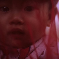 Asia, Vietnam, Hanoi,  Portrait of young boy covered with red gauze while riding on motorcycle near Hoan Kiem Lake