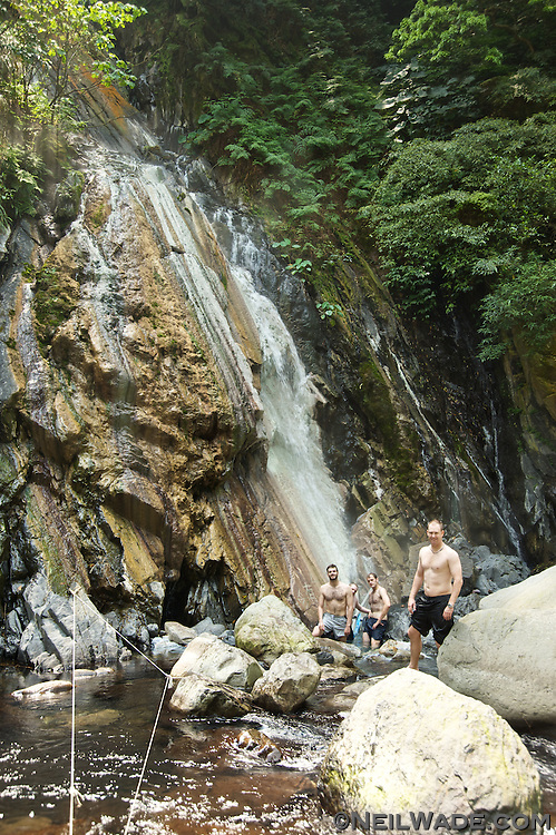 Tourists at a wild hot spring waterfall in the mountains of Taiwan.
