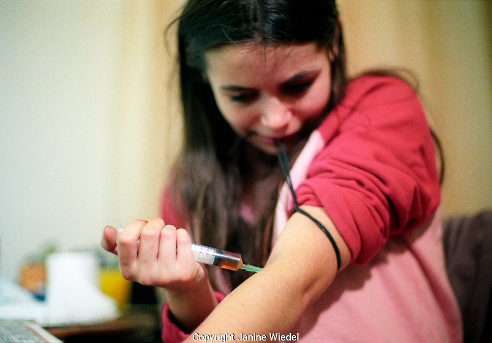 young woman injecting heroin.