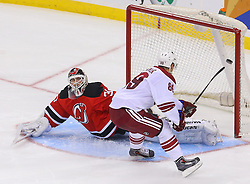 Mar 27, 2014; Newark, NJ, USA; Phoenix Coyotes left wing Mikkel Boedker (89) scores the game winning goal on New Jersey Devils goalie Martin Brodeur (30) in the shootout at Prudential Center. The Coyotes defeated the Devils 3-2 in a shootout.
