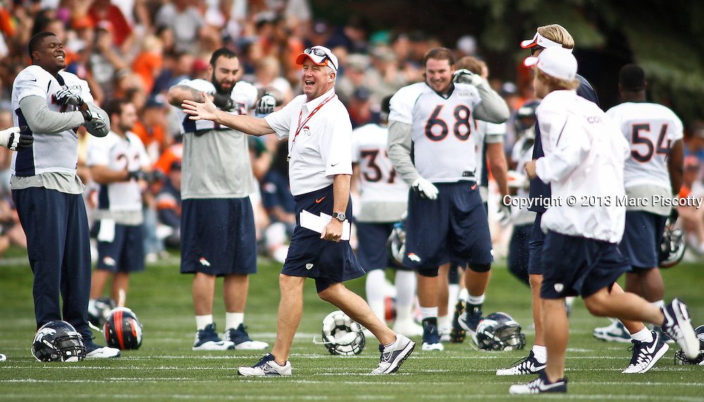 SHOT 7/25/13 9:21:23 AM - Denver Broncos head coach John Fox laughs with assistants and players during a stretching period on opening day of the team's training camp July 25, 2013 at Dove Valley in Englewood, Co.  (Photo by Marc Piscotty / © 2013)