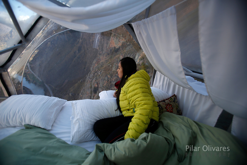 A guest looks the landscape inside a <br /> cabine at the Skylodge Adventure Suites in the Sacred Valley in Cuzco, Peru, August 14, 2015. The Skylodge is composed by three capsule suites hanging at the top of the 1300 feet mountain with a 300 degree view of the Valley. To sleep at Skylodge, people must climb 400 meters of Via Ferrata path and to leave the hotel people go down  a trail through ziplines. REUTERS/Pilar Olivares