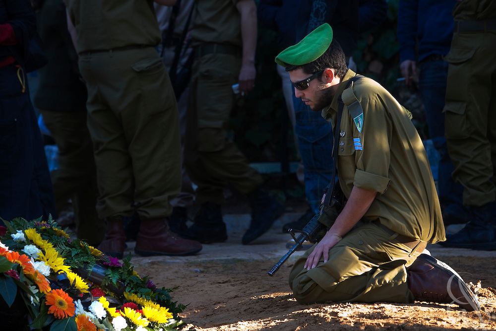 An Israeli soldier mourns at the grave of Staff Sgt. Nitai Stern, 21, who died in an operation in the Gaza Strip Monday, following his funeral at the Mt. Herzl cemetery in Jerusalem, Tuesday, Jan. 6, 2009. Stern and two other soldiers were killed when an Israeli tank shell mistakenly fired on their position in an apparent friendly-fire incident, Israeli sources said.