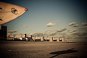 A surfer and his surfboard stand on Rockaway Beach casting a silhouette in front of the boardwalk, Queens, NY.