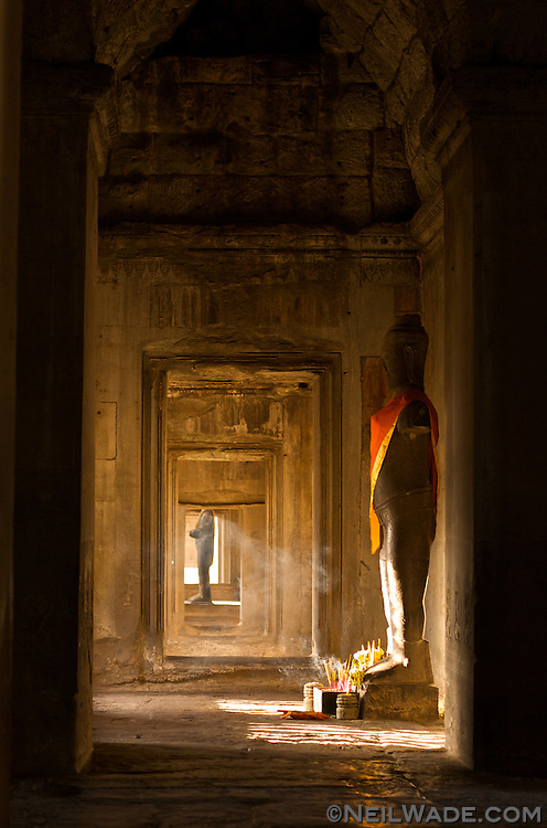 Offering of sweet smelling insence burn in front of an ancient Buddhist statue in Angkor Wat.