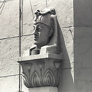 Unusual view of cast head of Egyptian deity affixed to side of building on University Ave, San Diego