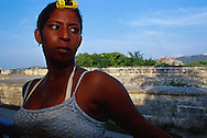 Una mujer morena, con un rollo en la cabeza. Vestida de camiseta y maquillada. Desde el balcón de su casa frente a la muralla. Cartagena de Indias,  2001 (Ramón Lepage / Orinoquiaphoto)     The fortified wall of Cartagena is in excellent condition and stretches more-or-less unbroken round a good portion of the Old Town. It is a pleasure for locals well as visitors to walk and observe the colonial architecture and excellent view of the Caribbean ocean..
