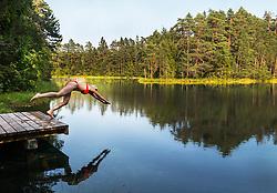 Woman jumping into green Äntu Great Lake in Estonia. Forest, water, pier.