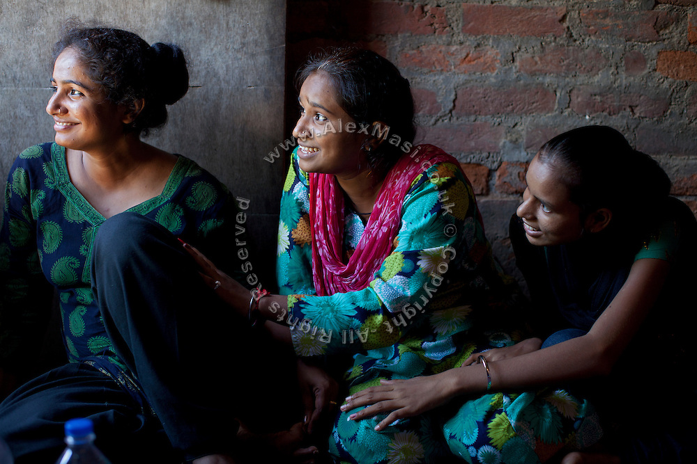 """Usha, 25, (left) and two other members of the Red Brigades are sitting inside Usha's home in Madiyaw colony, Lucknow District, Uttar Pradesh. The Red Brigades are a group of young women led by Usha, 25, who after an attempted rape began talking about abuse with her students, aged around 14 to 18 years old. Usha founded the Red Brigades in November 2010. They act in self-written plays on gender equality around villages and cities, take part to protests and also teach self-defence classes. Most of the girls in the group have experienced some kind of abuse in their past. They sing words such as """"all sisters are breaking all the rules, boundaries, come to bring a new world, change will come,"""" and """"for how long do we have to go through this?"""" and """"the country has freedom, but girls do not have freedom."""""""