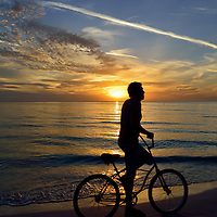 USA: Florida: Sarasota County: Sarasota: Silhouette of a bicyclist against a beautiful sunset on Lido Beach.