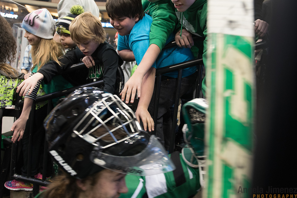 Young fans touch the helmet of an East Grand Forks player as the team leaves the ice after the Class A semifinal game between Mahtomedi and East Grand Forks (East Grand Forks won 5-2) at the Minnesota State High School League Boys' State Hockey Tournament at the Xcel Energy Center in St. Paul, Minnesota on March 6, 2015. <br />  <br /> <br /> Photo by Angela Jimenez for Minnesota Public Radio www.angelajimenezphotography.com