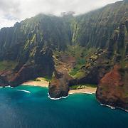 A power boat races between narrow canyons that meet the Pacific Ocean along the Na Pali coast of Kauai, Hawaii.