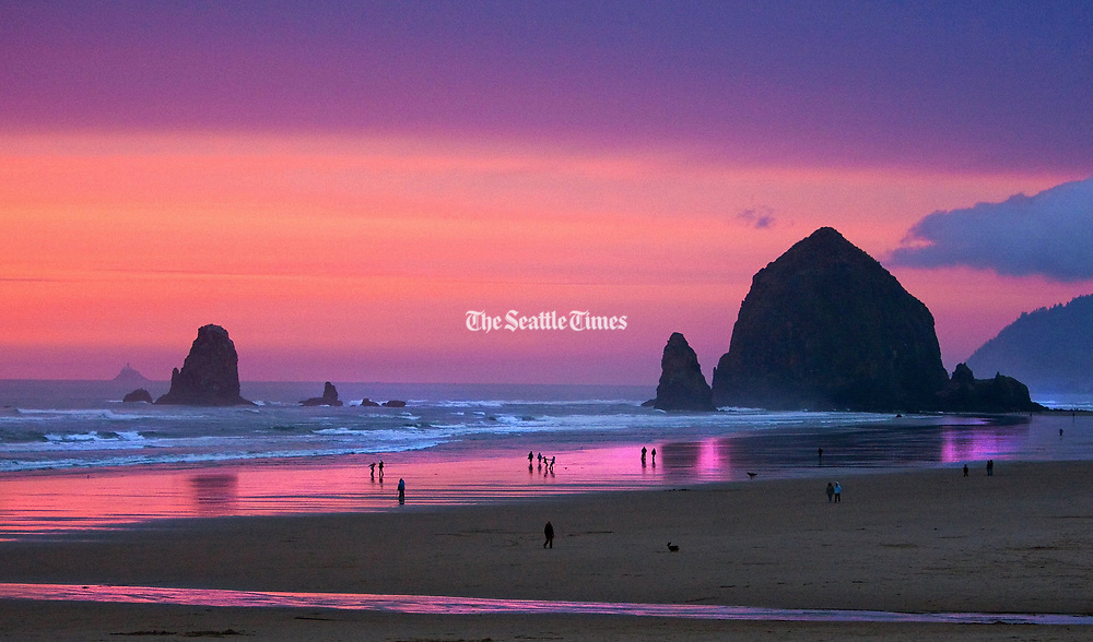 "Haystack Rock at Cannon Beach is a monolithic rock next to the beach. Tide pools around the rock support many intertidal animals, including starfish and sea anemones. The smaller formations next to Haystack are names the ""The Needles."" (Mike Siegel / The Seattle Times)"